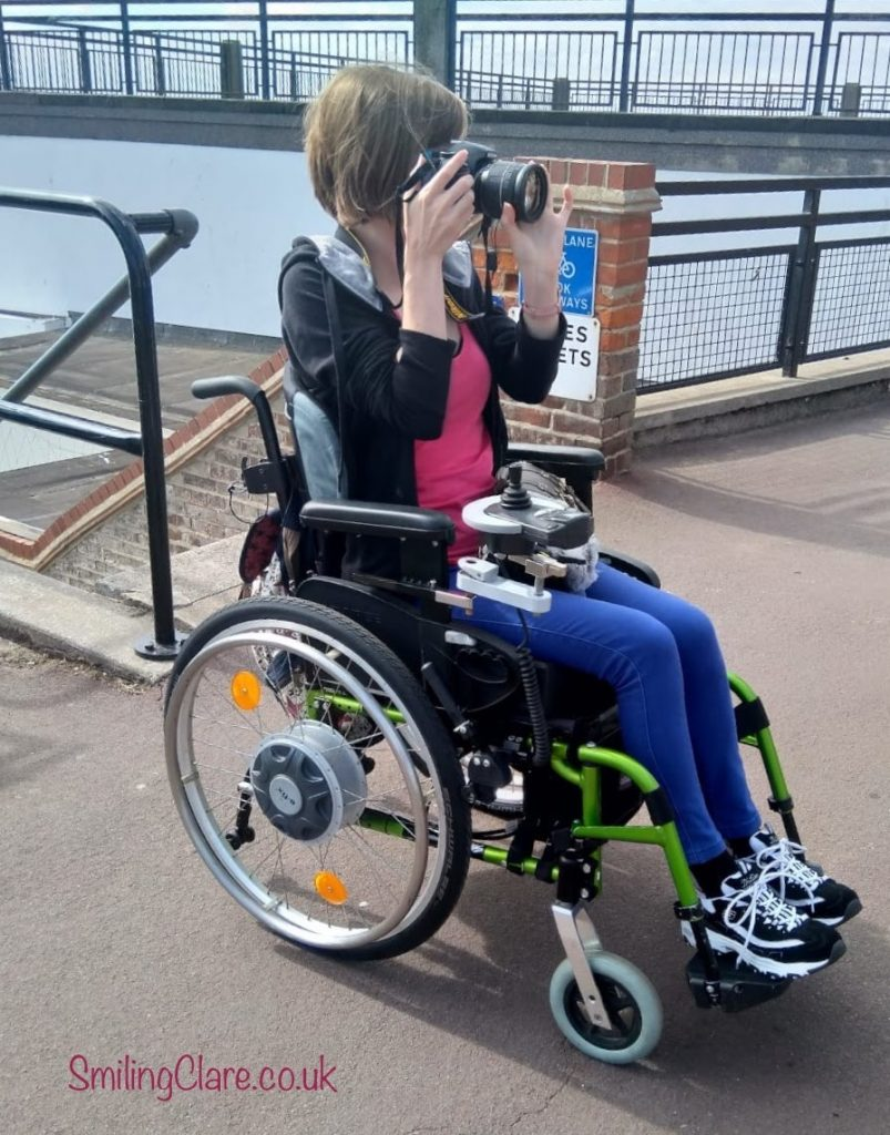 Slim woman in a green framed wheelchair, wearing bright blue trousers, a pink top and black hooded jacket, holding a camera up to her face taking a photograph
