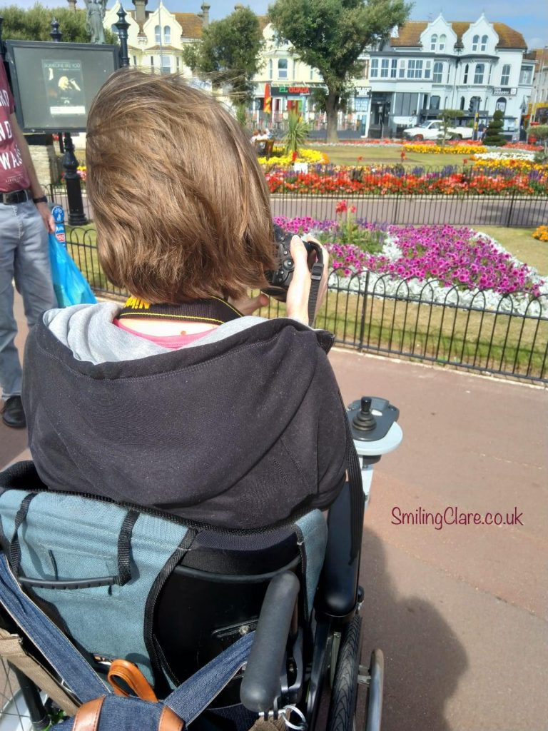 The back of a light brown haired woman, sat in a wheelchair, looking out toward a flowerbed and house in the distance which is in the background of the image