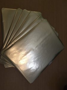 A picture of six placemats, after they have been wrapped in gold coloured paper